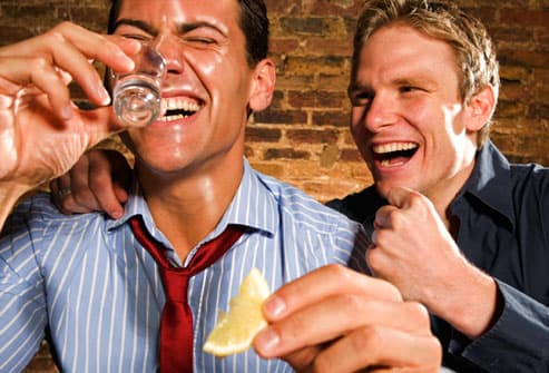Man doing shots of tequila and sweating heavily