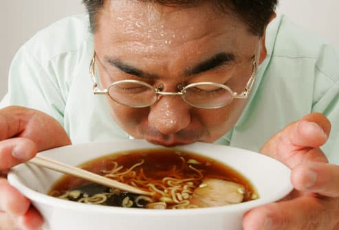 Man sweating profusely while eating spicy soup