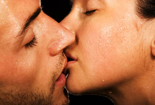 Young couple kissing and breaking into a sweat