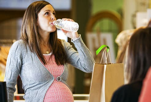 Thirsty pregnant woman drinking bottled water