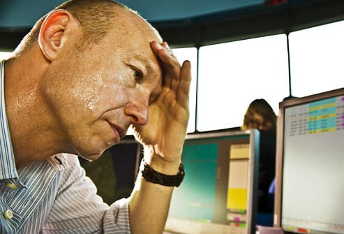 Stressed man sweating anxiously at the office