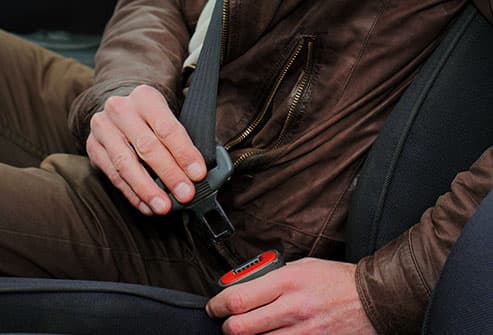 man buckling seat belt