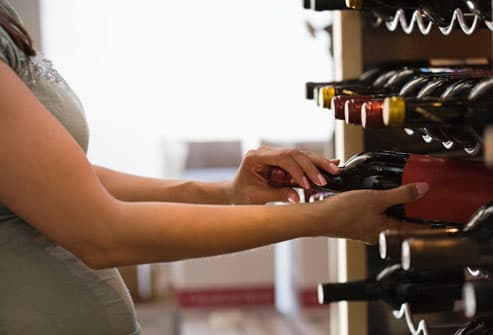 Pregnant woman looking at wine