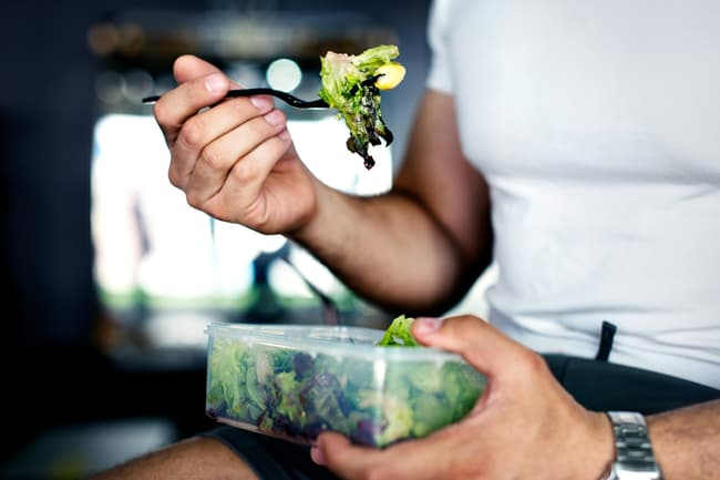 photo of man eating salad