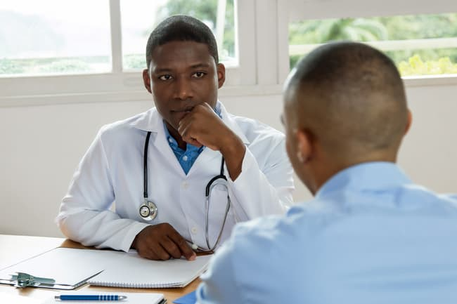 photo of man talking with doctor