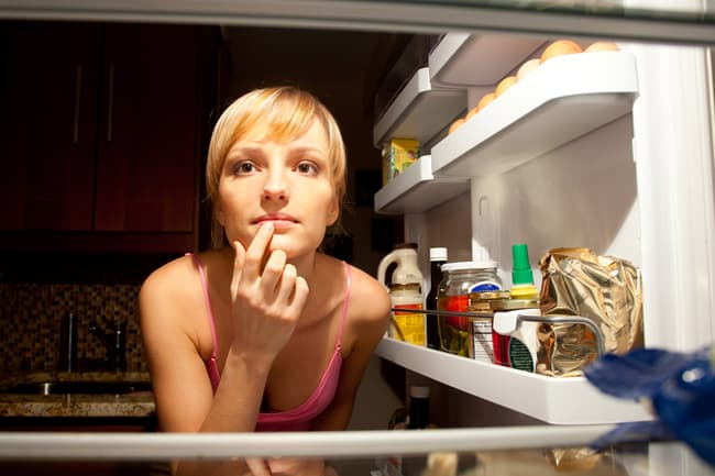 photo of woman looking for food in fridge