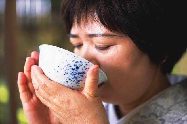 photo of woman drinking broth from bowl