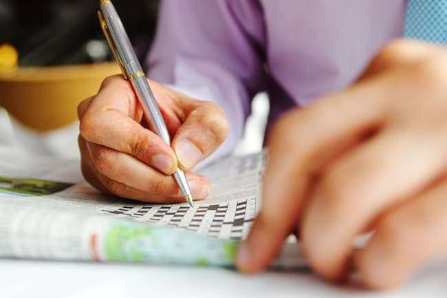 photo of person doing crossword puzzle
