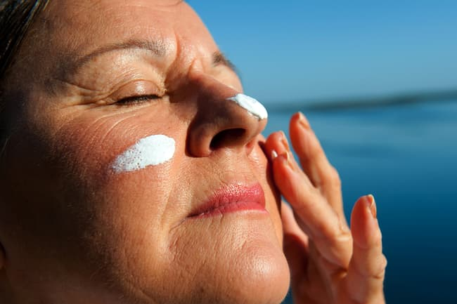 photo of mature woman applying sunscreen