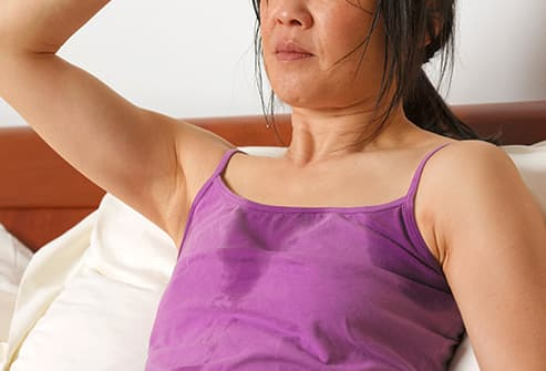 woman sweating on bed