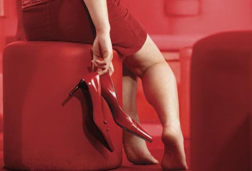 woman holding red shoes