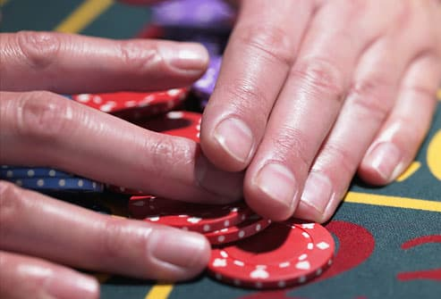 Man gathering pile of chips at roulette table