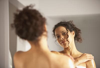 woman applying lotion while looking in mirror