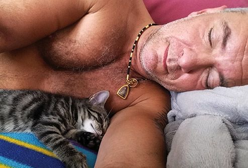man sleeping on side beside cat