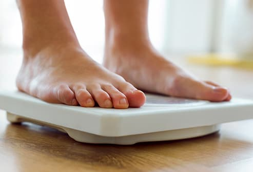 woman checking weight on home scale