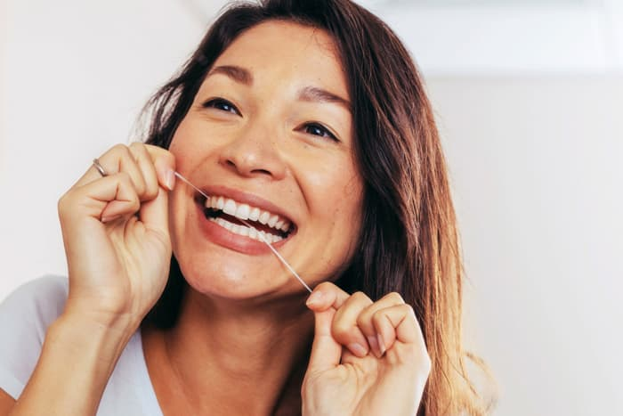 photo of woman flossing her teeth