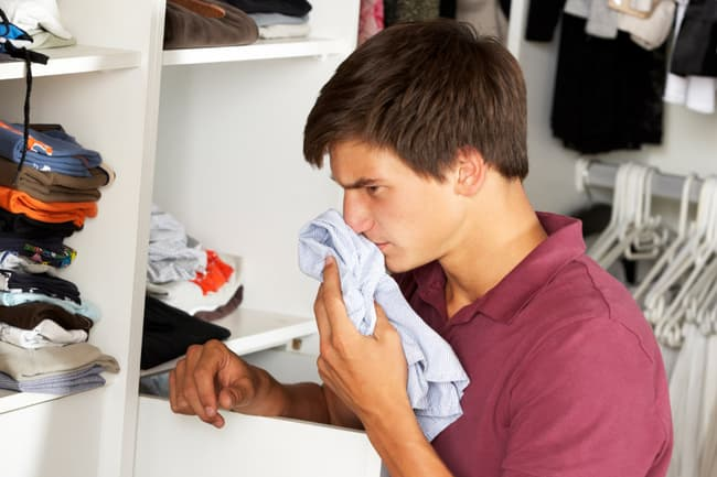 photo of young man giving laundry sniff test