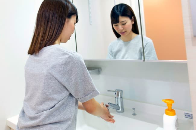 photo of young woman washing hands