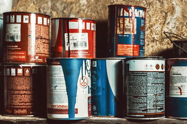 old paint cans on shelf