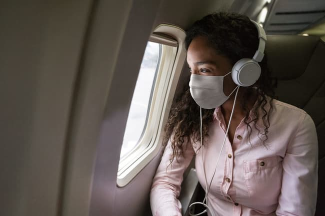 photo of woman looking out of plane window