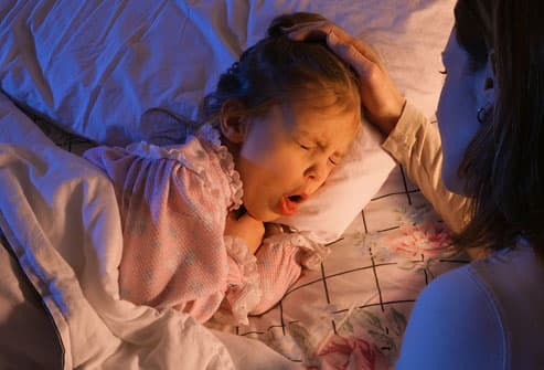 Mother tending to daughter coughing in bed
