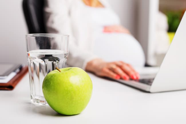 photo of pregnant woman with glass of water