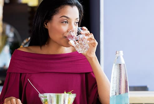 woman drinking water in restaurant