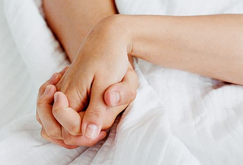 clasped hands in bed