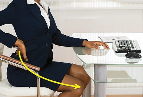 woman at desk with sore back
