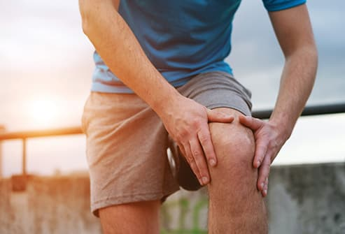 man holding sore knee early morning