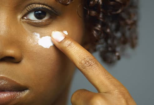 woman applying cream under eye