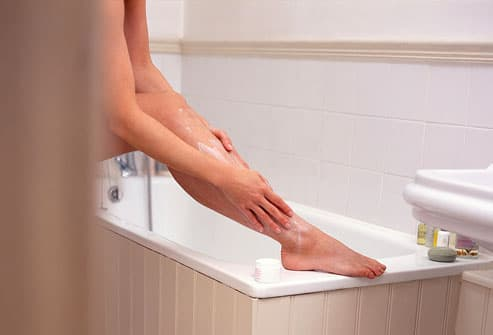 Woman resting foot on bath applying lotion