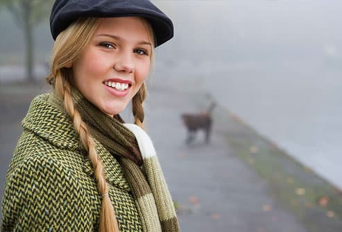 Young woman wearing braids, coat and hat