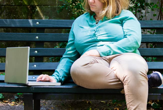 woman using laptop on park bench