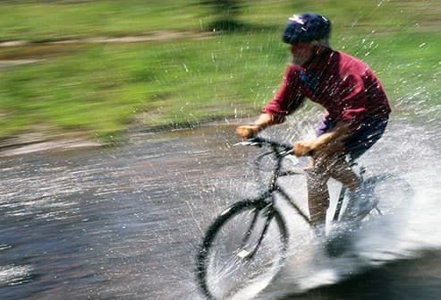 man cycling through stream