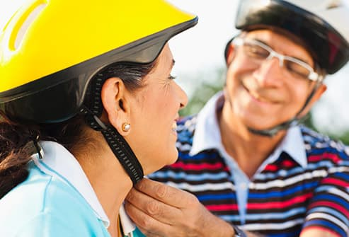 man fastening womans cycling helmet