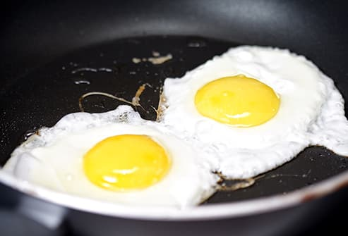 two eggs frying in pan
