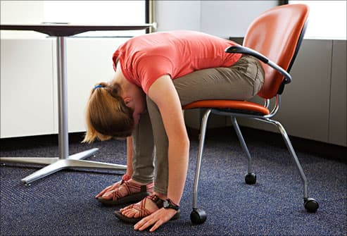 teen stretching in deskchair
