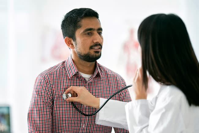 photo of doctor checking patient's heart
