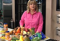 woman in kitchen with counter top of food