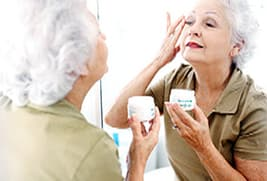 senior woman applying eye cream
