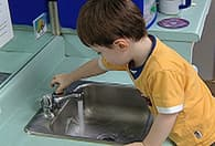 boy turning faucet on sink