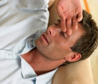 sick guy on couch with hand on head