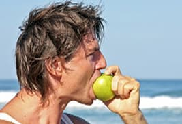 guy eating apple on beach