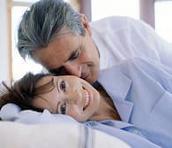 older couple snuggling in bed