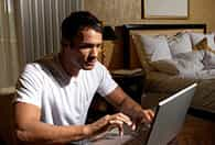 man working on laptop in bedroom