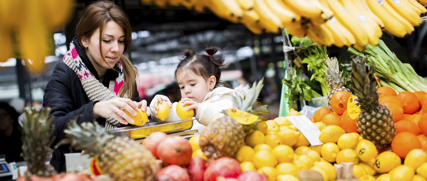 mother and daughter buying fruit