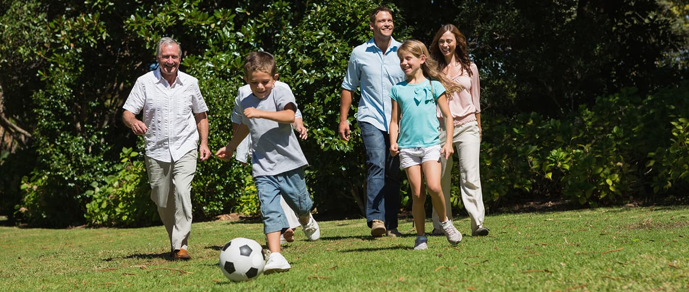 family in park walking and playing soccer