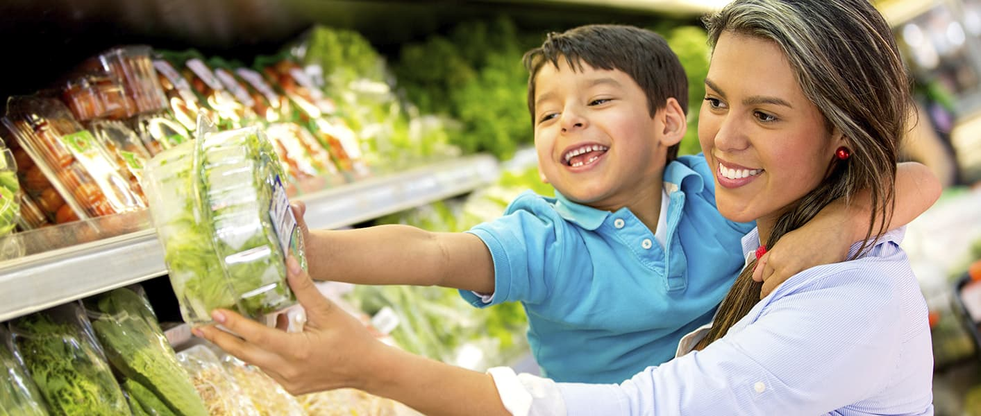 parent and child buying lettuce at grocery store