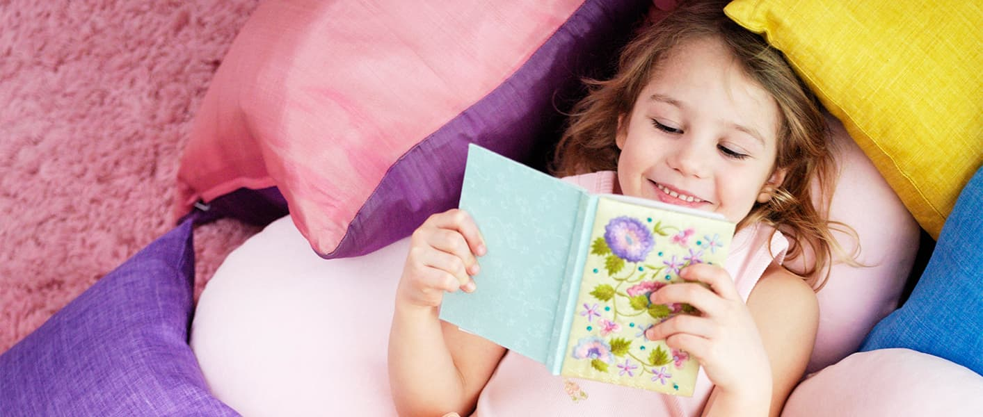 girl reading a book on top of pillows